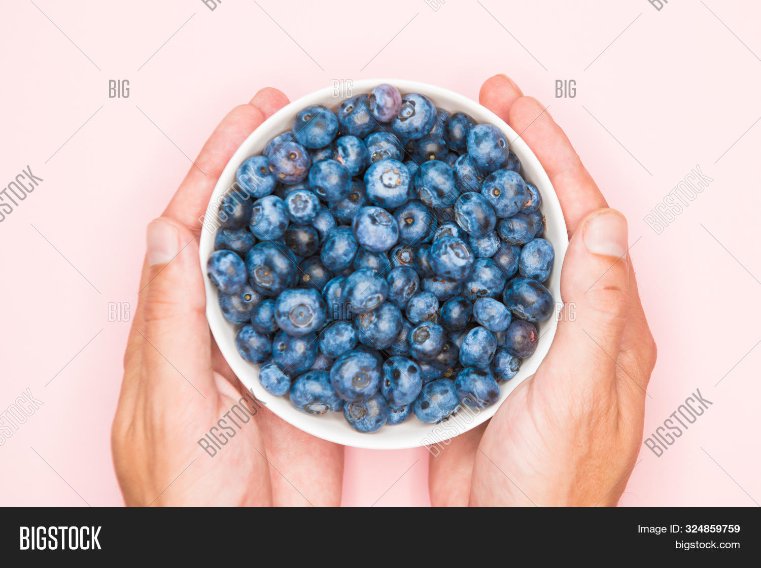 The Usefulness Of Blueberries. Closeup Of Blueberry Berries With Hands In A Light Dish Background. P