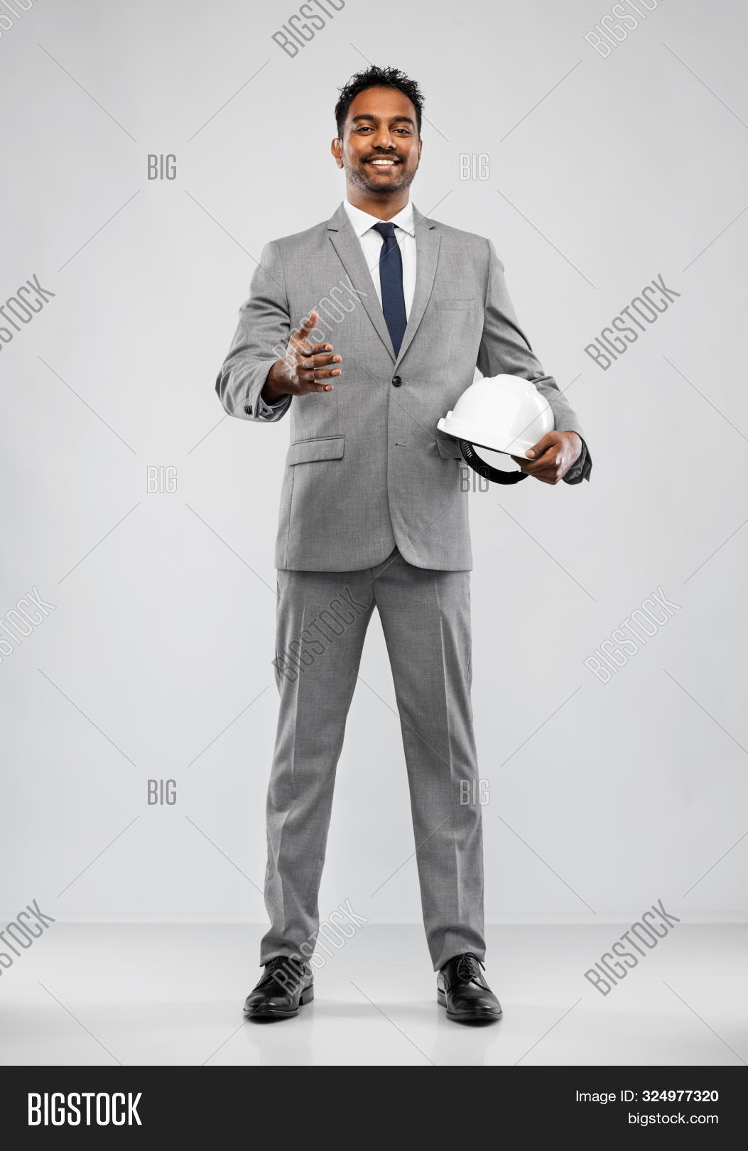 architecture, construction business and people concept - smiling indian male architect in helmet giv