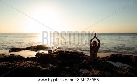 Yoga concept. Silhouette of woman practicing yoga, pranayama on the beach. Young woman sitting on the rock. View from back. Hands raising in namaste mudra. Sunset time. Yoga retreat, Bali. Lotus pose. stock photo