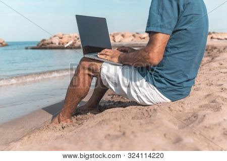 Adult male of mediterranean race using laptop while sitting on the sea beach. Freedom and travel concept stock photo