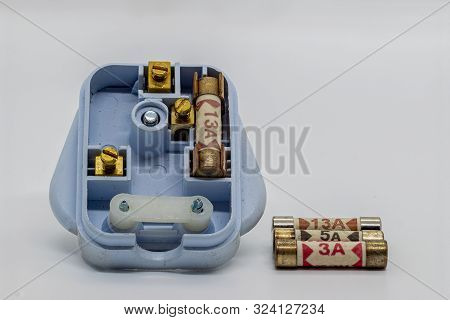 A UK 3 pin plug with 3 different rated fuses 3 Amps 5 Amps and 13 Amps on a white background stock photo