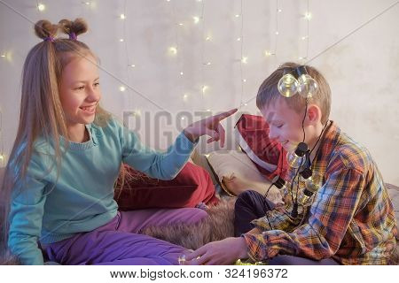 Boy and girl children friends playing with garland sitting on bed at home in Christmas interior. Cousin, siblings, child friendship. Celebrating new year xmax holiday, fun pastime in childhood. stock photo