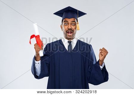 education, graduation and people concept - happy smiling indian male graduate student in mortar board and bachelor gown with diploma celebrating success over grey background stock photo