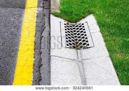 drainage system edge tray with concrete hatch for rainwater drainage into the sewer on side of tarmac road with a yellow marking and a green lawn. stock photo