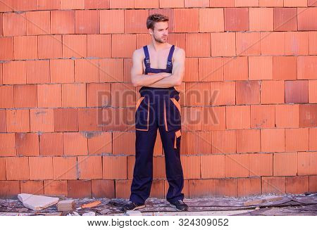 sexy mechanic. worker brick wall background. building skills and construction. man build house. skilled architect repair and fix. man builder in work clothes. professional repairman. turnkey project stock photo