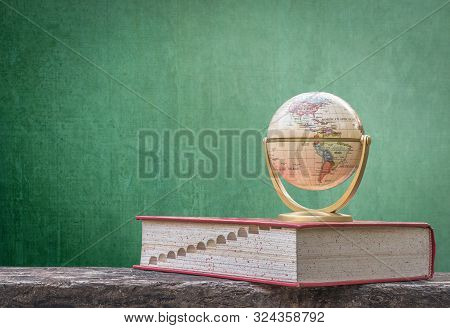 Global education, study aboard, international educational academic program for student concept with world globe, textbook and black school teacher chalkboard background with copy space stock photo