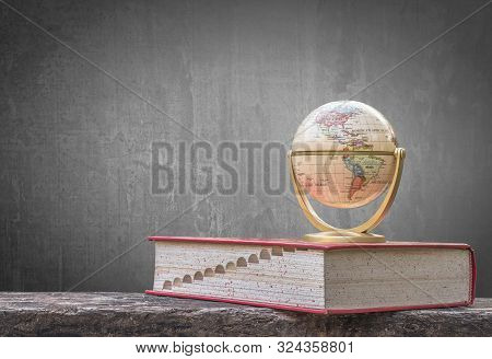 Global education, study abroad, international educational student academic program concept with world globe, textbook and black school teacher chalkboard background with copy space stock photo