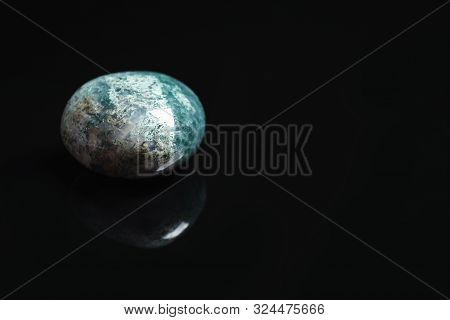 Beautiful moss agate gemstone on black background. Space for text stock photo