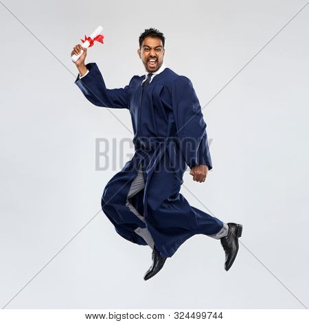 education, graduation and people concept - happy smiling indian male graduate student in bachelor gown with diploma celebrating success and jumping over grey background stock photo