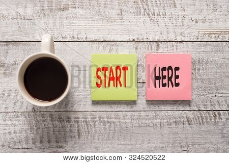Handwriting text writing Start Here. Concept meaning telling someone this is beginning point to go from to destination Stationary placed next to a cup of black coffee above the wooden table. stock photo