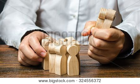 A man grabs a figurine of people from the crowd. Hiring employees. Market Segmentation and Niche Conquest. Human resources. Enticement of workers and customers from a competitor. predatory competition stock photo