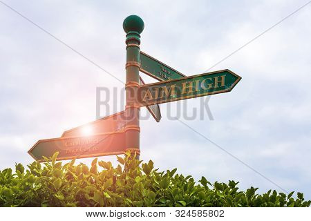 Text sign showing Aim High. Conceptual photo go for best job school or activity Asking someone to dream big Green road sign on the crossroads with cloudy sky and green grass in the background. stock photo