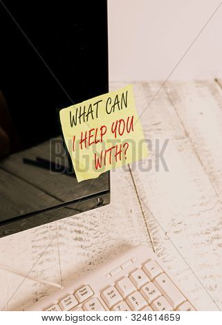 Word writing text What Can I Help You With Question. Business concept for Offering assistance Experts advice ideas Notation paper taped to black computer monitor screen near white keyboard. stock photo