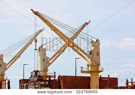 Cranes used for lifting cargo onto ships at a busy wharf stock photo