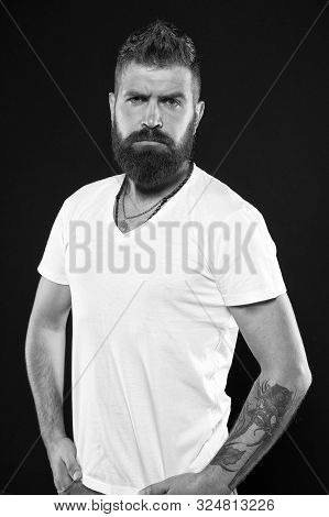 His barber has a master hand. Serious barber on black background. Bearded man with shaped beard and mustache hair after visiting barber. Mens barber or hairdresser. stock photo