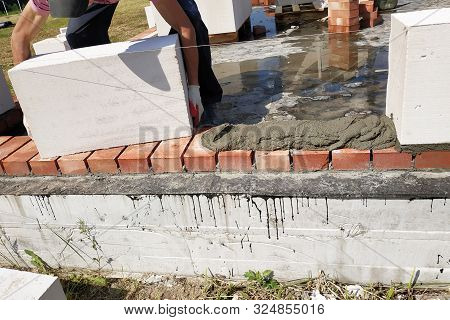 The worker begins the first row of masonry construction in white gas blocks. stock photo