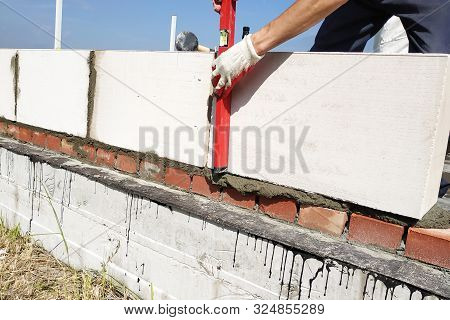 The worker measures the work out wall with a level. stock photo