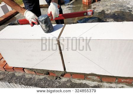 The master uses the level in the construction and masonry of the house in the countryside. stock photo
