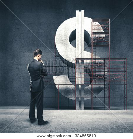 Businessman Standing In Concrete Room And Thinking About Business, Money Concept