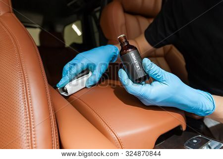 Applying a nano-ceramic coating for interior leather on the car's seat brown upholstery by a worker in blue gloves with a sponge and bottle of chemical composition. Auto service industry. stock photo
