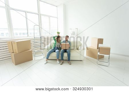 Cheerful joyful young couple charming girl and handsome man holding a box with things and a pot with a plant while moving to a new apartment. Housewarming and mortgage concept. stock photo