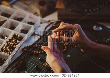 Young woman is holding semi precious stone in hands, close up photoshoot. stock photo