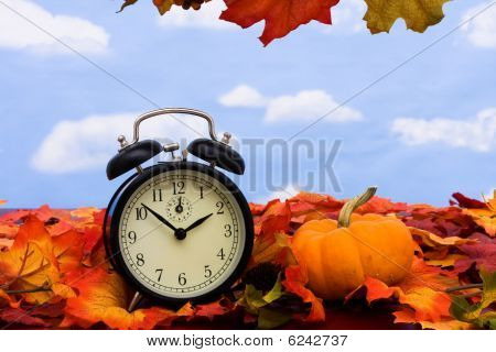 Fall coloured leaves with a black clock on a sky background Fall Leaves stock photo