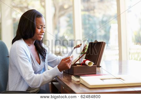 Woman Looking At Letter In Keepsake Box On Desk stock photo