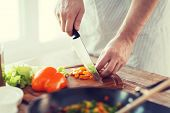 cooking, nourishment and home idea - close up of male hand cutting pepper on cutting board at home
