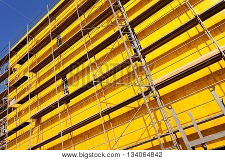 yellow protective tarpaulins and scaffolding on a building stock photo
