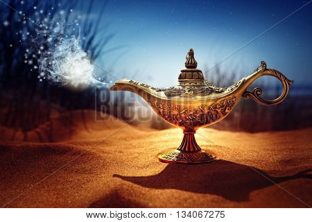 Magic lamp in the desert from the story of Aladdin with Genie appearing in blue smoke concept for wi