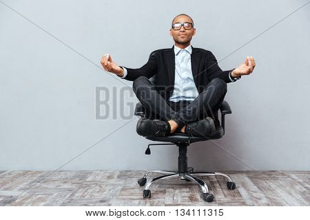 Relaxed handsome african young man sitting and meditating on office chair