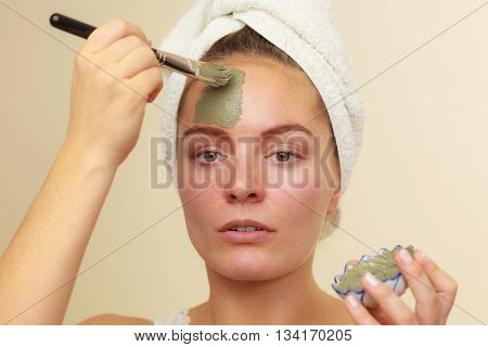 Skin care. Woman applying with brush clay mud mask to her face. Girl taking care of oily complexion. Beauty treatment. stock photo