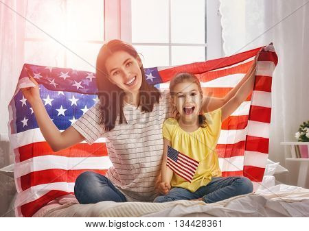 Patriotic holiday. Happy family, mother and her daughter child girl with American flag at home. USA