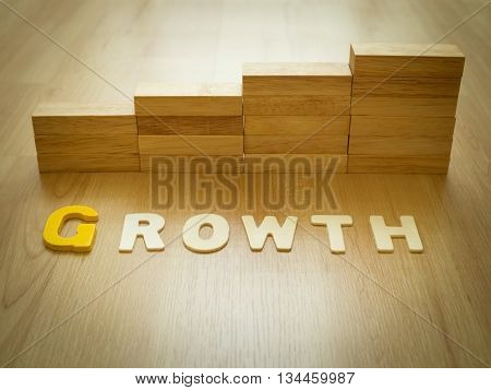 Growth word on wooden floor with wood block stacking as step stair in background. Business concept for growth success process. Growth in career path concept. Vintage filter and selective focus. stock photo