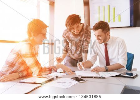 startup business young creative  people group brainstorming on meeting at office using laptop and tablet computer to note ideas plans and projects sunrise or sunset with sun flare  in background stock photo