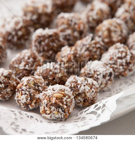 White plate full of delicious raw protein balls. Healthy sweets for sport people. Homemade dessert. Raw sweets made of nuts coconut dates and cacao