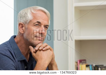 Portrait of thoughtful senior man at home. Pensive retired man smiling and looking up. Happy mature man thinking about his retirement. stock photo