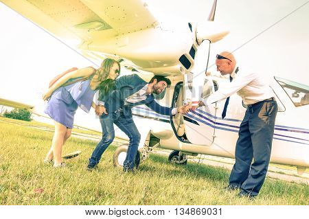 Young couple getting on lightweight airplane with captain welcome - People boarding on excursion plane - Alternative adventure vacation concept - Vintage filter with sunflare halo and tilted horizon stock photo