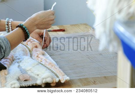 Weaving on a loom. Closeup woman's hands runs the yarn through the threads of the loom stock photo