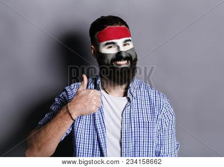 Portrait of man with the flag of Egypt painted on his face. Football or soccer team fan, sport event, faceart and patriotism concept. Studio shot at white background, copy space stock photo