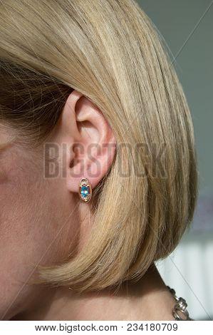 Golden earring with blue gem - topaz and few diamonds in model's ear stock photo