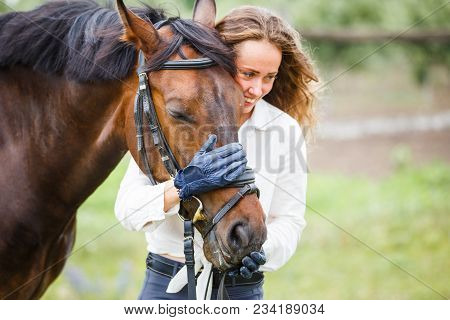 Young happy rider woman with her bay horse. Portrait of smiling girl with her stallion in paddock on summer day stock photo
