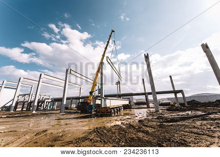 Details of construction site with crane lifting prefabricated concrete framework, unloading and cargo details stock photo