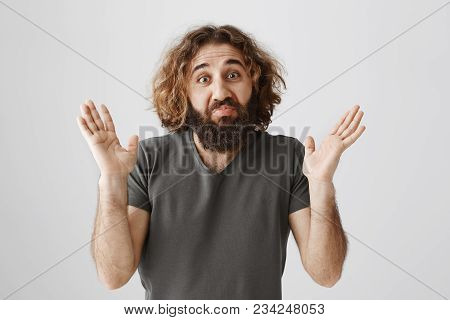 Uninvolved man wash hands of this case. Portrait of handsome clueless eastern male model raising palms and shrugging with gloomy smile, being unaware and indifferent to topic of conversation. stock photo