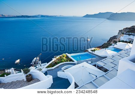 White architecture at Santorini island. Swimming pool in romantic luxury hotel at Oia town. Beautiful panoramic view on the mediterranean sea. stock photo