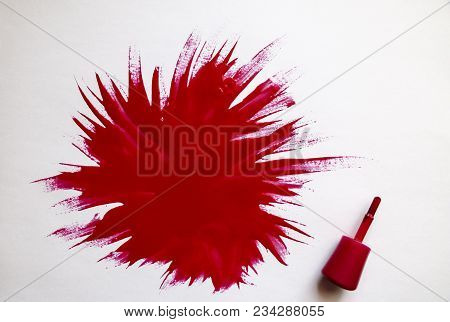red nail polish. explosion of color. Brush with red nail polish with large spot of varnish on  white background. stock photo
