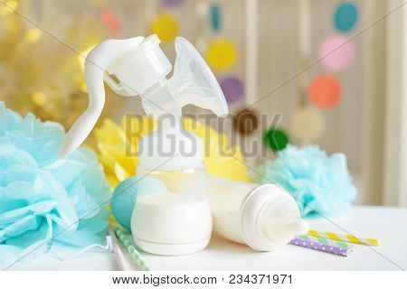 Baby bottle with breast milk, various festive paper decor in front of baby bed. It's a boy or baby birthday celebration concept. Baby shower concept. stock photo