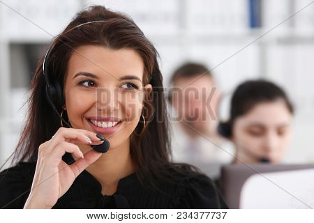 Three call centre service operators at work. Portrait of smiling pretty brunette woman at workplace employment effective mediation negotiation participation solve problem real time aid job concept stock photo