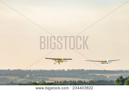 Small light-engine sport plane flying in the evening sky pulls on a rope the glider plane. Flight over the green hazy plain. stock photo